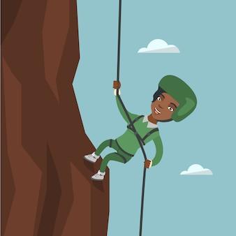 Afrikanerin, die einen berg mit seil klettert.