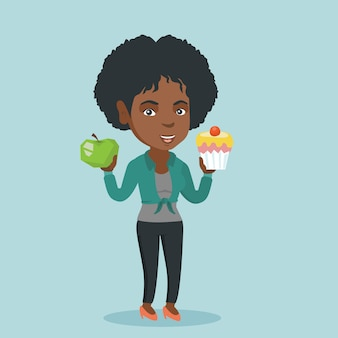 Afrikanerin, die zwischen apfel und kleinem kuchen wählt.