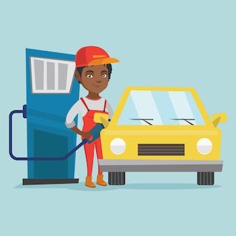 Afrikanische arbeitskraft der tankstelle ein auto betankend.