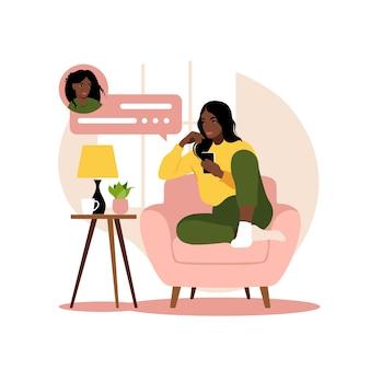 Afrikanische frau, die auf sofa mit telefon sitzt. arbeiten im telefon. freiberufliche, online-bildung oder social-media-konzept. flacher stil. abbildung auf weiß isoliert.