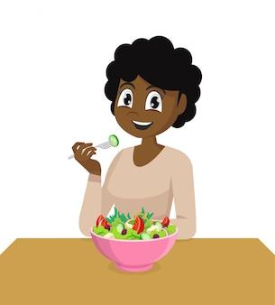 Afrikanische frau, die gesunden gemüsesalat isst.