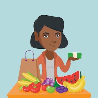 Afrikanische frau mit geld und lebensmitteleinkäufen.