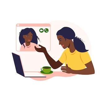 Afrikanische freundinnen chatten online. mädchen sitzt auf einem stuhl vor einem laptop und spricht mit freund