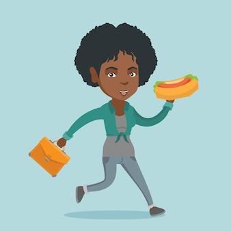 Afrikanische geschäftsfrau, die hotdog auf der flucht isst