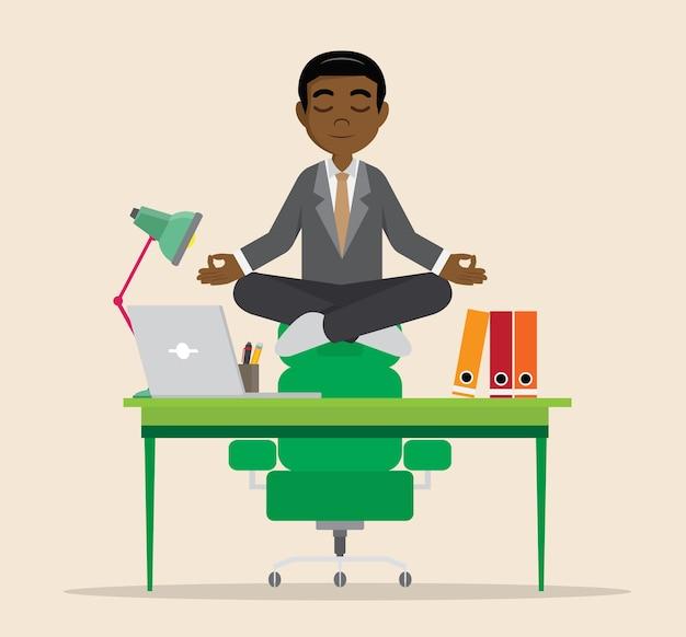 Afrikanischer geschäftsmann, der auf schreibtisch meditiert.