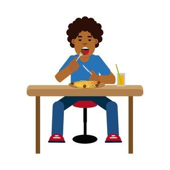 Afrikanischer junge, der spaghettis mit fleischklöschen isst