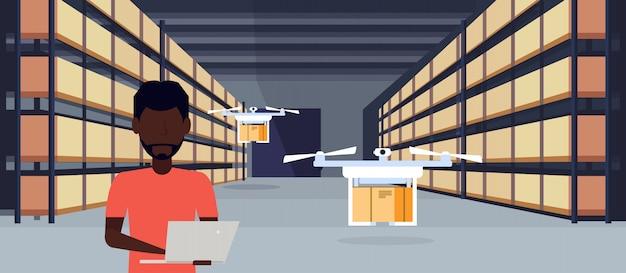 Afrikanischer mann betreiber drohne fliegt arbeitslager interieur mit laptop paket box
