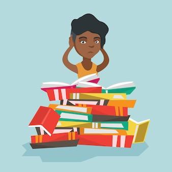 Afrikanischer student, der in einem enormen stapel von büchern sitzt.