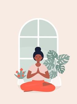 Afro frau, die in lotussitz zu hause durch topfpflanze sitzt