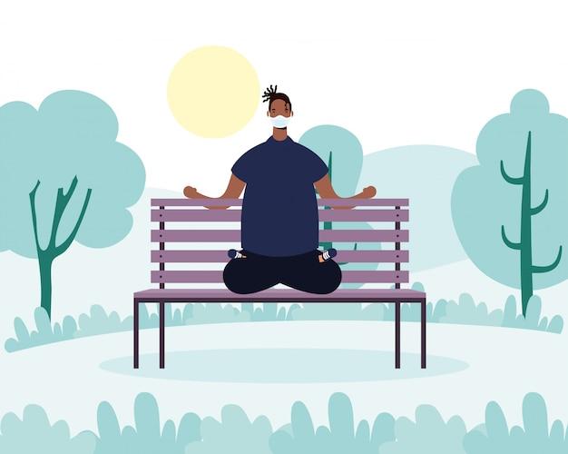 Afro junger mann, der medizinische maske trägt, die yoga im parkstuhl praktiziert