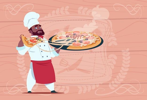 Afroamerikaner-chef cook holding pizza-lächelnder karikatur-chef in der weißen restaurant-uniform über hölzernem strukturiertem hintergrund