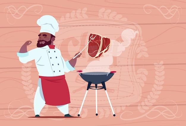Afroamerikaner-chef-koch-grill-fleisch auf bbq-karikatur-restaurant-chef in der weißen uniform über hölzernem strukturiertem hintergrund