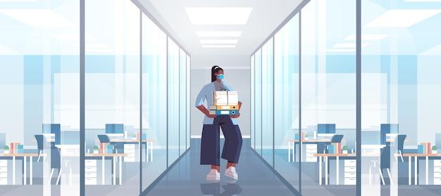 Afroamerikaner-geschäftsfrau, die schutzmaske trägt, um coronavirus-pandemie-covid-19-quarantänekonzept zu verhindern moderne bürokorridor-innenausstattung in voller länge