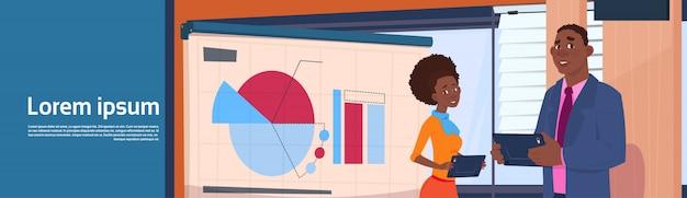 Afroamerikaner-geschäftsmann and businesswoman holding presentation-stand über brett mit diagrammen