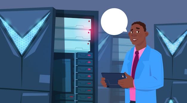 Afroamerikaner-geschäftsmann, der an digital-tablet in der modernen datenbank-mitte oder im server-raum-bus arbeitet