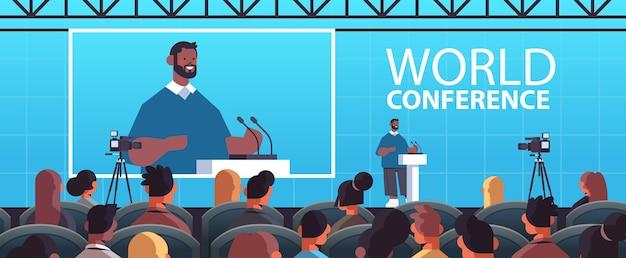 Afroamerikaner-geschäftsmann, der rede an der tribüne mit mikrofon auf innenweltillustration des internationalen weltkonferenz-hörsaals des unternehmens hält