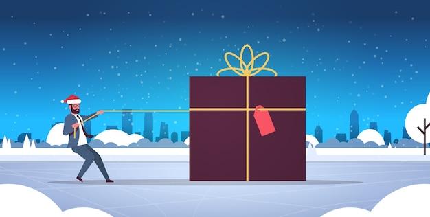 Afroamerikaner geschäftsmann in santa hut ziehen große geschenkbox weihnachten neujahr winterferien feier konzept schneefall stadtbild hintergrund flache illustration
