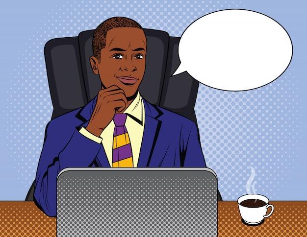 Afroamerikaner kerl im anzug, der am schreibtisch arbeitet