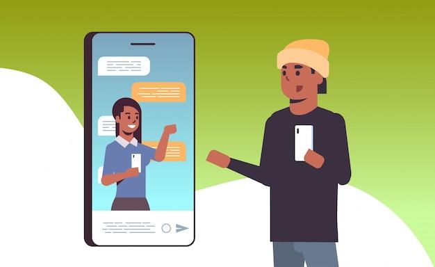 Afroamerikaner-mann, der smartphone-online-konferenzvideoanruf mit kommunikationskonzept des sozialen netzwerks der kollegin verwendet