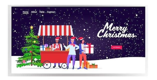 Afroamerikaner-mann in der weihnachtsmütze, die geschenkboxen verkauft, die leute einkaufen und geschenke auf weihnachtsmarkt oder schönen winterferien kaufen