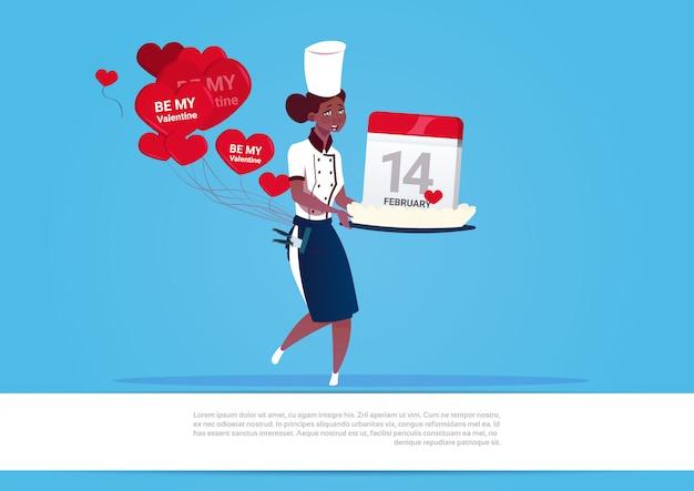 Afroamerikaner-weiblicher koch holding cake with calendar für glückliches valentinstag-feier-14.februar-feiertags-konzept