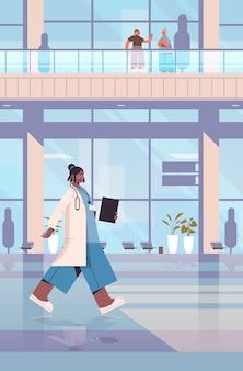 Afroamerikanerarzt im einheitlichen medizinischen arbeiter mit stethoskop und zwischenablage gesundheitsmedizin konzept krankenhausgebäude außenvertikale