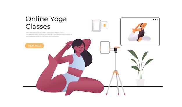 Afroamerikanerfrau, die dehnübungen macht, während sie online-video-trainingsprogramm sieht