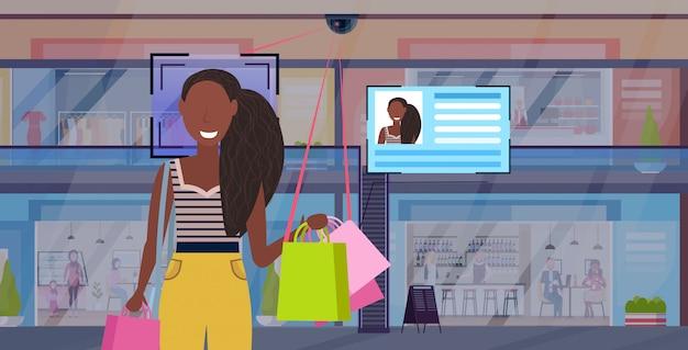 Afroamerikanerfrau, die einkaufstaschen-gesichtserkennungskonzeptüberwachungskameraüberwachungs-cctv-system des modernen einkaufszentrums-supermarktinnenraums horizontales porträt hält