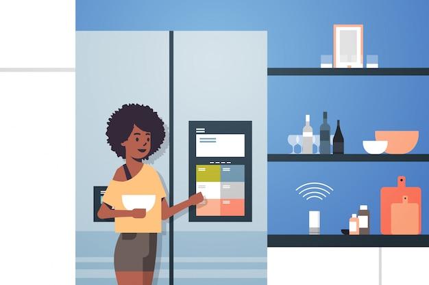 Afroamerikanerfrau, die kühlschrankbildschirm mit intelligenter lautsprecher-spracherkennung berührt