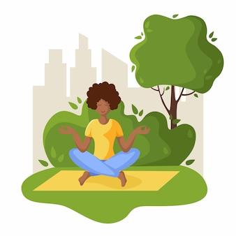 Afroamerikanerfrau, die yoga im park im freien tut, mädchen ist in der lotosstellung, die übung tut