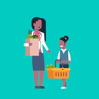 Afroamerikanerfrau mit der tochter, die papiertüte und einkaufskorb voll von den lebensmittelgeschäft-produkten hält