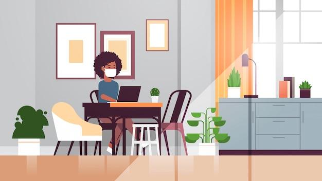 Afroamerikanerin in schutzmaske mit laptop coronavirus pandemie quarantäne konzept arbeit von zu hause aus online-bildung freiberufliche moderne wohnzimmer interieur in voller länge horizontal