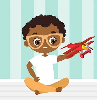 Afroamerikanerjunge mit gläsern und spielzeugfläche. junge spielt mit dem flugzeug