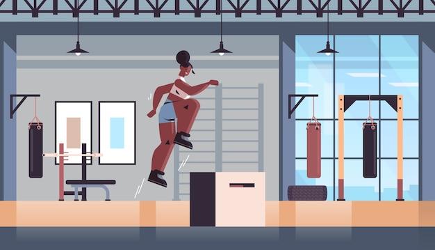 Afroamerikanermädchen, das springende kniebeugen auf kniebeuge-box tut, die fitness-training gesundes lebensstilkonzept modernes fitnessstudio-studio-interieur ausarbeitet