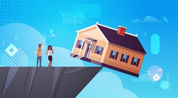 Afroamerikanermann-frauenpaare, die das nachhausefallen in der abgrundschuld nach dem hausimmobilien-wohnungskrisengeschäft des hypothekenzins-konkurskonzeptes horizontal in voller länge betrachten