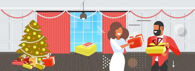 Afroamerikanerpaar, das geschenkgeschenkboxen einander frohe weihnachten winterferienfeierkonzept modernes wohnzimmerinnenporträt horizontale vektorillustration gibt