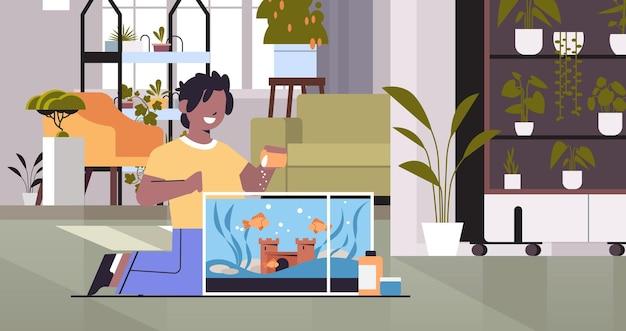 Afroamerikanischer junge, der fische im aquarium füttert, haustierfreundschaft mit haustierkonzept, wohnzimmerinnenraum, horizontale vektorillustration in voller länge