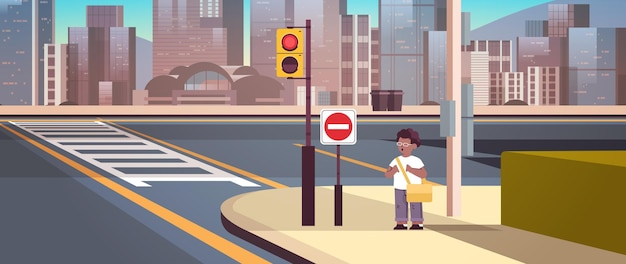Afroamerikanischer schuljunge mit rucksack, der auf der stadtstraße in der nähe des roten stoppschildes verkehrssicherheit steht