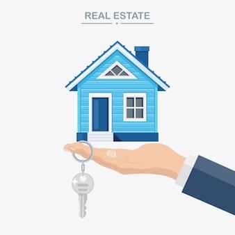 Agent hält zu hause und schlüssel in der hand. hypothek, umgang mit immobilien, miete von immobilien