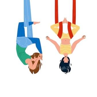 Air yoga trainingsübung mädchen paar vektor. junge frauen, die zusammen luft-yoga ausüben, damen fliegen in der anti-schwerkraft-hängematte. charaktere sportler sport aktivität flache cartoon illustration