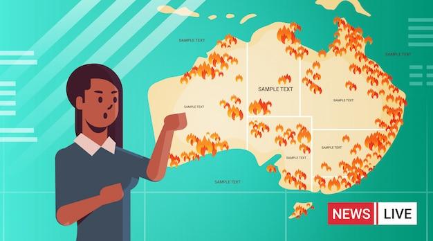 Aktuelle nachrichten afroamerikaner reporter live-brodcasting karte von australien mit symbolen der buschfeuer saisonale waldbrände trocknen die globale erwärmung naturkatastrophe konzept porträt brennen