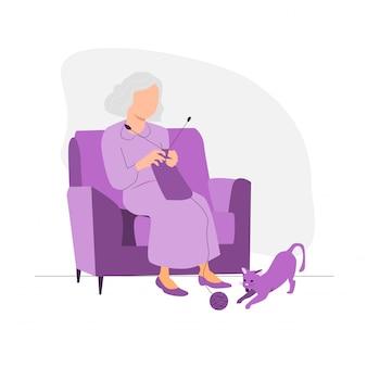 Alte frau strickt auf dem sofa.