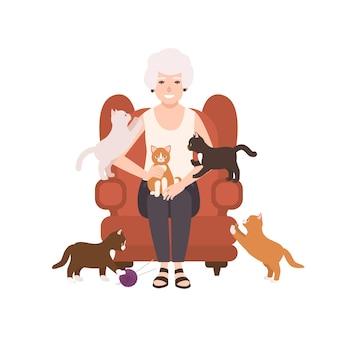 Alte glückliche dame, die im bequemen sessel sitzt, umgeben von katzen