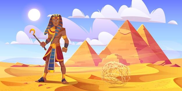 Alter ägyptischer pharao mit stab in der wüste mit pyramiden. vektorkarikaturillustration der landschaft mit gelben sanddünen, pharao-gräbern, figur des königs von ägypten und tumbleweed