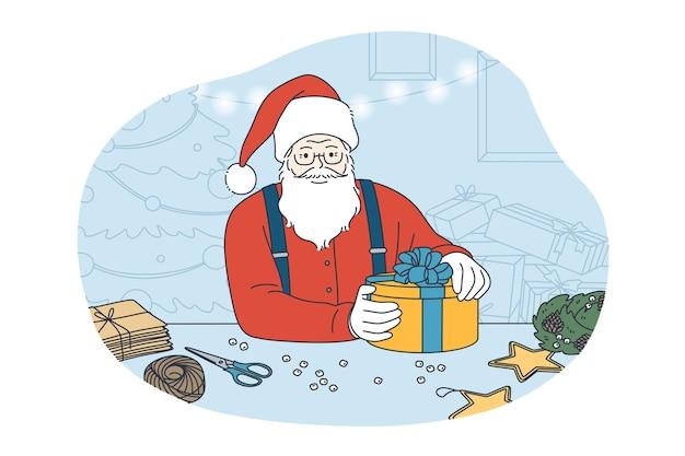 Alter lustiger bärtiger weihnachtsmann in traditioneller tracht und hut, die geschenkbox hält, die für heiligabend über haufen von kisten vorbereitet