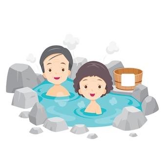 Alter mann und frau, die im japanischen onsen, thermalbad entspannen