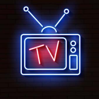 Altes neonfernsehen mit antenne auf backsteinmauer