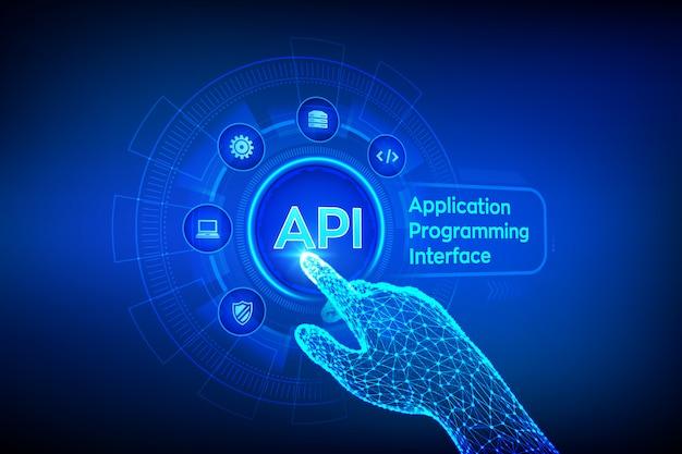 Api. anwendungsprogrammierschnittstellenkonzept auf virtuellem bildschirm. roboterhand, die digitale schnittstelle berührt.