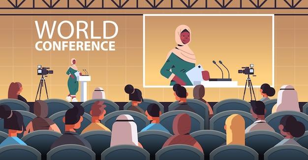 Arabische ärztin, die rede an der tribüne mit mikrofon medizinische konferenzbesprechung medizin gesundheitswesen konzept hörsaal innen horizontale illustration hält