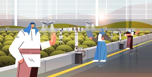 Arabische bauern kontrollieren landwirtschaftliche drohnen-sprühgeräte quad-copter, die fliegen, um chemische düngemittel im gewächshaus zu sprühen smart farming innovation technologiekonzept horizontale vektorillustration